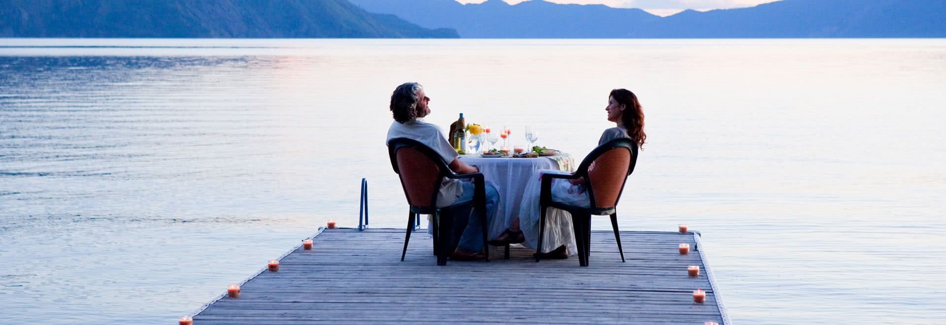 A couple dine together at a lake